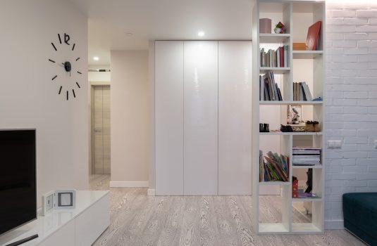 Шкаф с полками по середине комнаты в светлых оттенках